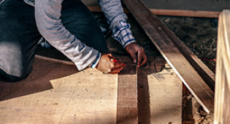 Image of Man measuring boards of wood